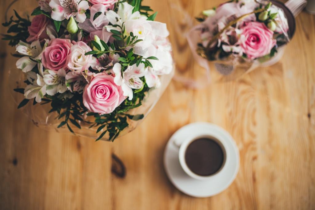 Ylhäältä kuvattu lähikuva kahdesta kukkakimpusta ja kahvikupista, jotka on aseteltu kauniisti vaaleapintaiselle puupöydälle