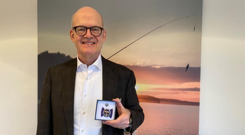 Harri Nordqvist hymyilee kuvassa ja näyttää kädessään rautaista ansiomerkkiä kameralle